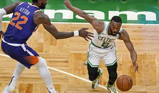 Boston Celtics guard Kemba Walker (8) drives against Phoenix Suns center Deandre Ayton (22) during the second half of an NBA basketball game Thursday, April 22, 2021, in Boston. (AP Photo/Elise Amendola)