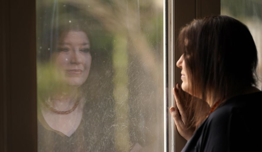Keri Wegg is reflected in a sliding glass door as she looks outside her home in Westfield, Ind., on Monday, March 22, 2021. The Indiana nurse came down with COVID-19 in the summer of 2020; her condition spiraled downward, and her life was saved only by grace of a double lung transplant. The road to normal is a long one, but she's bolstered by the love and support of her husband and sons, and by her own indomitable spirit. (AP Photo/Charles Rex Arbogast)