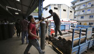 Workers unload empty oxygen cylinders returning from hospitals at a gas supplier facility in Bengaluru, India, Wednesday, April 21, 2021. India has been overwhelmed by hundreds of thousands of new coronavirus cases daily, bringing pain, fear and agony to many lives as lockdowns have been placed in Delhi and other cities. (AP Photo/Aijaz Rahi)
