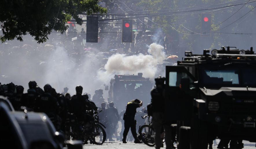 FILE - In this July 25, 2020, file photo, smoke rises as police clash with protester during a Black Lives Matter protest near the Seattle Police East Precinct headquarters in Seattle. Mayors, county executives or even the governor would have to give their approval before police could use tear gas to quell riots under a compromise reached in the Washington Legislature. A conference committee of the House and Senate met Thursday, April 22, 2021, to reconcile versions of a police tactics bill already approved by each chamber. (AP Photo/Ted S. Warren, File)