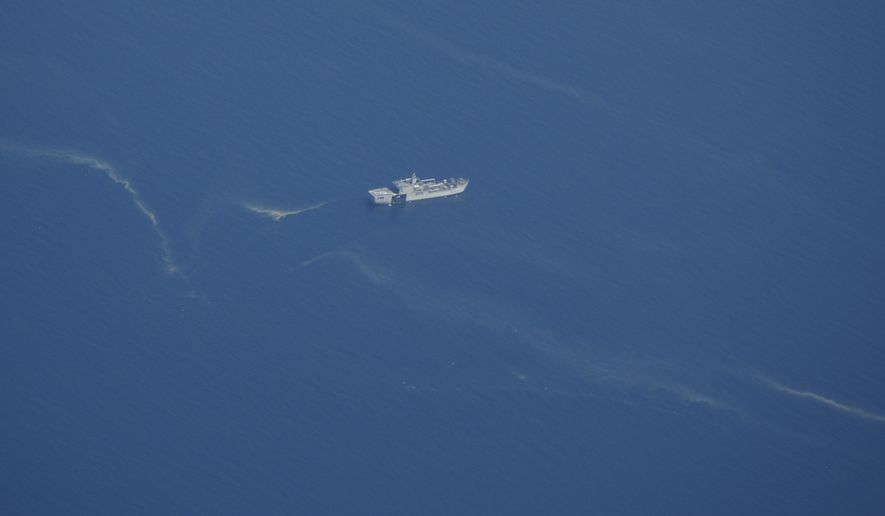 An Indonesian Navy ship sails near what appears to be oil slicks during the search for submarine KRI Nanggala that went missing while participating in a training exercise on Wednesday, in this aerial photo taken from a maritime patrol aircraft of 800 Air Squadron of the 2nd Air Wing of Naval Aviation Center (PUSPENERBAL) over the Bali Sea, Indonesia, Friday, April 23, 2021. Indonesian navy ships scoured the waters off Bali on Friday as they raced against time to find the submarine that disappeared two days ago and has less than a day's supply of oxygen left for its 53 crew. (AP Photo/Eric Ireng)