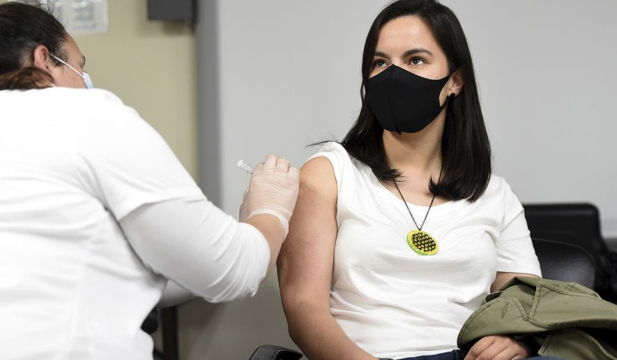 Madeline Gent from Aspinwall gets her second dose of the Moderna vaccine from Cristina McCarthy, a student nurse from Carlow University during the Pittsburgh Mercy's South Side vaccination clinic, Friday, April 23, 2021, in Pittsburgh. (Pam Panchak/Pittsburgh Post-Gazette via AP)