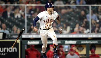 Houston Astros' Carlos Correa tosses his bat after hitting a RBI single against the Los Angeles Angels during the third inning of a baseball game Thursday, April 22, 2021, in Houston. (AP Photo/David J. Phillip)