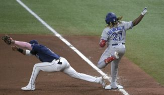 Tampa Bay Rays first baseman Yandy Diaz (2) stretches for the throw from third for the out on Toronto Blue Jays' Vladimir Guerrero Jr. (27) during the fifth inning of a baseball game Friday, April 23, 2021, in St. Petersburg, Fla. (AP Photo/Phelan M. Ebenhack)