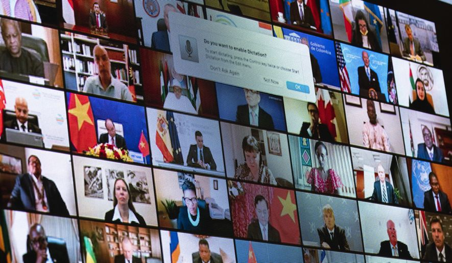 World leaders are shown on a screen as President Joe Biden speaks to the virtual Leaders Summit on Climate, from the East Room of the White House, Friday, April 23, 2021, in Washington. (AP Photo/Evan Vucci)