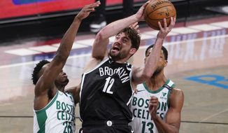 Brooklyn Nets forward Joe Harris (12) goes to the basket against Boston Celtics forward Aaron Nesmith (26) and center Tristan Thompson (13) during the second half of an NBA basketball game Friday, April 23, 2021, in New York. (AP Photo/Mary Altaffer)