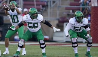 File-This Sept. 21, 2019, file photo shows Oregon offensive linemen Shane Lemieux (68) and Penei Sewell (58) blocks for quarterback Justin Herbert (10) against Stanford during the first half of an NCAA college football game in Stanford, Calif.  Caleb Farley of Virginia Tech was the first top prospect to make the decision that has added a whole new layer of uncertainty to the annual crapshoot that is the NFL draft. Farley had plenty of players follow his lead, including several others set to be high draft picks next week like LSU receiver Chase, Oregon tackle Sewell, Northwestern tackle Rashawn Slater and Penn State linebacker Micah Parsons.(AP Photo/Tony Avelar, File)