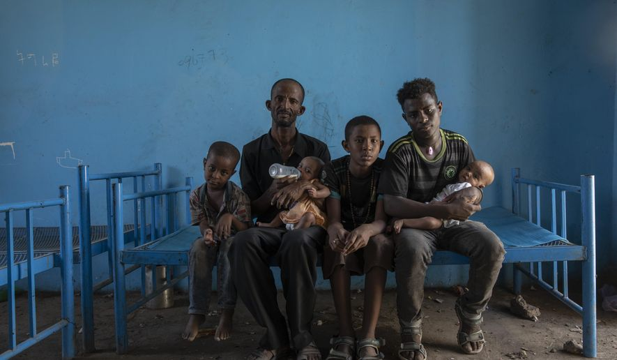 """Tigrayan refugee Abraha Kinfe Gebremariam, 40, second left, sits for a photograph with his sons, Micheale, 5, left; Daniel, 11, center; his 19-year-old brother-in-law, Goytom Tsegay, second right, and his 4-month-old twin daughters Aden, right, and Turfu Gebremariam, on his lap, inside their family's shelter in Hamdayet, eastern Sudan, near the border with Ethiopia, on March 23, 2021. A fellow refugee, Mulu Gebrencheal, a mother of five, has become an informal adviser, offering guidance on the babies' care. Abraha and his sons are quick learners, she said. But she mourns for the twins and the death of their mother. """"Even the hug of a mother is very sweet,"""" she said. """"They've never had this. They never will."""" (AP Photo/Nariman El-Mofty)"""