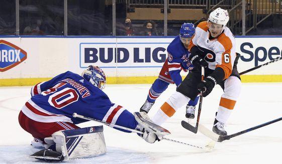 New York Rangers' Alexandar Georgiev (40) makes a third-period save against Philadelphia Flyers' Travis Sanheim (6) during an NHL hockey game Friday, April 23, 2021, in New York. (Bruce Bennett/Pool Photo via AP)