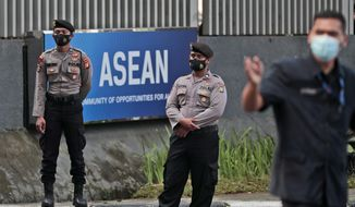 Police officers stand guard outside the Association of Southeast Asian Nations (ASEAN) Secretariat ahead of a leaders' meeting in Jakarta, Indonesia, Friday, April 23, 2021. The 10-member Association of Southeast Asian Nations is scheduled to hold a special summit to discuss Myanmar on Saturday. (AP Photo/Dita Alangkara)