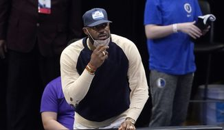Los Angeles Lakers forward LeBron James watches from the bench as the team plays the Dallas Mavericks in the first half of an NBA basketball game in Dallas, Thursday, April 22, 2021. (AP Photo/Tony Gutierrez)