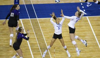 Kentucky's Elise Goetzinger (11) spikes the ball from a set by Madison Lilley (3) against Washington during a semifinal in the NCAA women's volleyball championships Thursday, April 22, 2021, in Omaha, Neb. (AP Photo/John Peterson)