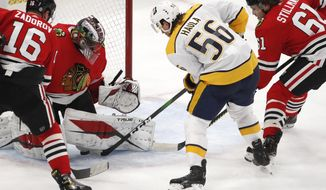 Nashville Predators left wing Erik Haula (56) tries to get the puck past Chicago Blackhawks goaltender Malcolm Subban (30) as Blackhawks' Nikita Zadorov (16) and Riley Stillman (61) defend during the second period of an NHL hockey game Friday, April 23, 2021, in Chicago. (AP Photo/Jeff Haynes)