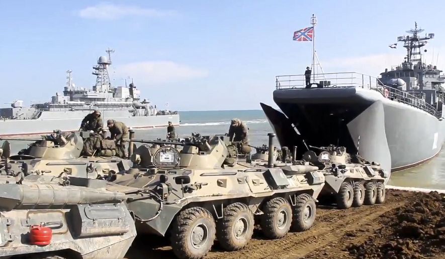 This handout photo taken from a video released on Friday, April 23, 2021, by Russian Defense Ministry Press Service shows the Russian military's armored vehicles roll into landing vessels after drills in Crimea. Russian Defense Minister Sergei Shoigu on Thursday ordered troops back to their permanent bases after a massive military buildup that caused Ukrainian and Western concerns. (Russian Defense Ministry Press Service via AP)