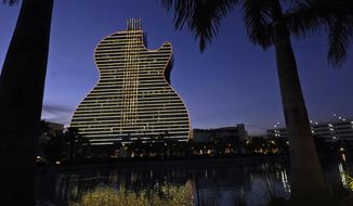 FILE- In this Jan. 19, 2021, file pot, The Guitar Hotel at Seminole Hard Rock Hotel & Casino Hollywood is illuminated at night in Hollywood, Fla. Florida Gov. Ron DeSantis reached an agreement with the state's Seminole Tribe on Friday, April 23, 2021, that would greatly expand gambling in the state, including the introduction of legalized sports wagering. (AP Photo/Wilfredo Lee)