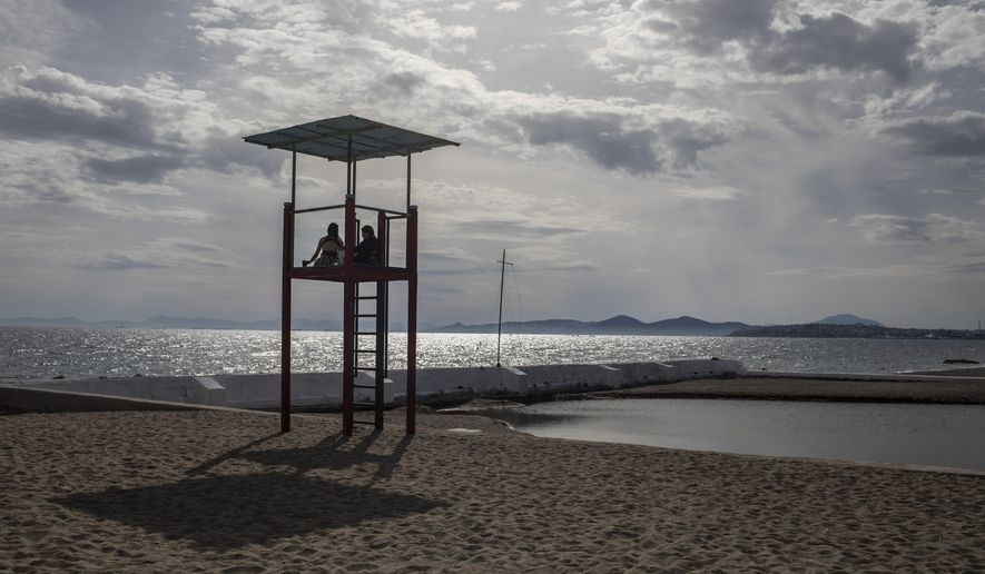 Two women sit on life-guard post, in Alimos beach, a seaside suburb of Athens, on Friday April 23, 2021. Easter holidays are often celebrated with relatives outside Athens and other cities, but the government has said COVID-19 infection levels remain too high to allow free travel.(AP Photo/Petros Giannakouris)