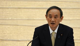 Japanese Prime Minister Yoshihide Suga declares a state of emergency for Tokyo and three other prefectures during the government task force meeting for the COVID-19 measures at the prime minister's office Friday, April 23, 2021, in Tokyo. (AP Photo/Eugene Hoshiko, Pool)