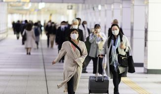 People wearing face masks to help curb the spread of the coronavirus walk toward a train station in Tokyo on Friday, April 23, 2021. (AP Photo/Hiro Komae)