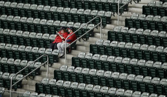 Fans sit in the upper deck seats in Truist Park upon learning a baseball game between the Atlanta Braves and the Arizona Diamondbacks had been postponed on Saturday, April 24, 2021, in Atlanta. The Diamondbacks and Braves will play in a traditional doubleheader Sunday. (AP Photo/Ben Margot) **FILE**
