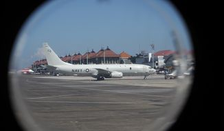 A U.S. Navy's P-8 Poseidon is parked on the tarmac at Ngurah Rai International Airport as seen from the window of Indonesian Navy's maritime patrol aircraft of 800 Air Squadron of the 2nd Air Wing of Naval Aviation Center (PUSPENERBAL), in Bali, Indonesia, Saturday, April 24, 2021. The American reconnaissance plane was expected to join the search for Indonesian navy submarine KRI Nanggala that went missing after its last reported dive Wednesday off the resort island. (AP Photo/Eric Ireng)
