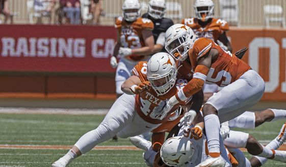 Texas defenders Jake Ehlinger, left, and B.J. Foster, right, tackle Kayvontay Dixon (16) during the first half of the Texas Orange and White Spring Scrimmage football game in Austin, Texas, Saturday, April 24, 2021. (AP Photo/Michael Thomas) **FILE**
