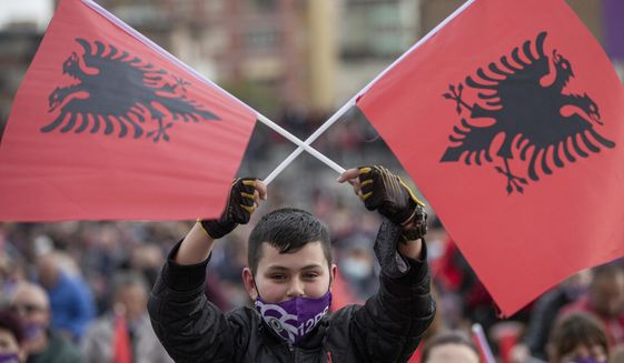 Supporter of socialist party waving Albanian flag participates in the political rally in city of Durres, Albania on Friday, April 23, 2021.Albania holds parliamentary elections on Sunday amid the virus pandemic and a bitter political rivalry between the country's two largest political parties but that will serve as a key milestone in the country's next step toward European Union membership. (AP Photo/Visar Kryeziu)