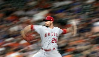 In this image taken with a slow shutter speed, Los Angeles Angels starting pitcher Andrew Heaney throws against the Houston Astros during the seventh inning of a baseball game Friday, April 23, 2021, in Houston. (AP Photo/David J. Phillip)