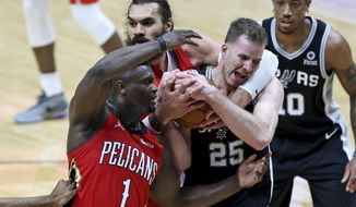 San Antonio Spurs center Jakob Poeltl (25) fights for a rebound with New Orleans Pelicans forward Zion Williamson (1) and center Steven Adams (12) during the first half of an NBA basketball game in New Orleans, Saturday, April 24, 2021. (AP Photo/Rusty Costanza)