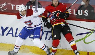 Montreal Canadiens' Corey Perry, left, checks Calgary Flames' Nikita Nesterov during the first period of an NHL hockey game Friday, April 23, 2021, in Calgary, Alberta. (Jeff McIntosh/The Canadian Press via AP)