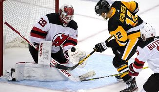 New Jersey Devils goaltender Mackenzie Blackwood (29) gloves a rebound before Pittsburgh Penguins' Zach Aston-Reese (12) can get his stick on it during the second period of an NHL hockey game in Pittsburgh, Saturday, April 24, 2021. (AP Photo/Gene J. Puskar)