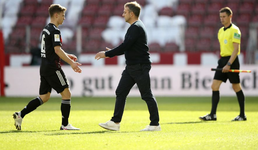 Bayern's head coach Hans-Dieter Flick, right, and Bayern's Joshua Kimmich shake hands after the German Bundesliga soccer match between FSV Mainz and FC Bayern Munich in Mainz, Germany, Saturday, April 24, 2021. (AP Photo/dpa via AP)