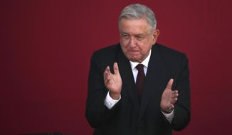 FILE - In this Feb. 9, 2021 file photo, Mexican President Andres Manuel Lopez Obrador applauds during a ceremony at Chapultepec Castle in Mexico City. Mexico announced Saturday, April 24, 2021, that Lopez Obrador will hold talks with U.S. Vice President Kamala Harris on May 7 to discuss migration, amid an increase in underage migrants at the U.S. southern border. (AP Photo/Marco Ugarte, File)