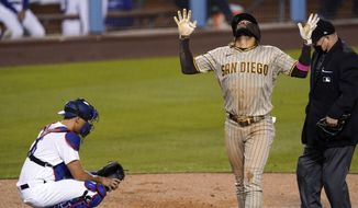 San Diego Padres' Fernando Tatis Jr., center, celebrates after hitting a solo home run as Los Angeles Dodgers catcher Austin Barnes, left, watches along with home plate umpire Todd Tichenor during the third inning of a baseball game Friday, April 23, 2021, in Los Angeles. (AP Photo/Mark J. Terrill)
