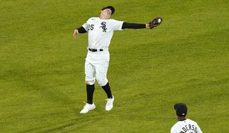 Chicago White Sox's Andrew Vaughn makes an awkward catch of a fly ball hit by Texas Rangers' Nate Lowe during the fifth inning of a baseball game Friday, April 23, 2021, in Chicago. (AP Photo/Charles Rex Arbogast)