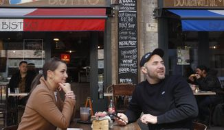 A couple sit in the outside terrace of a bar in Budapest, Hungary, Saturday, April 24, 2021. Hungarians had their first taste of normality in nearly six months Saturday as the outdoor terraces of restaurants and bars filled up in the country's capital, marking the newest round of openings in a country that's been among the hardest hit by the pandemic. (AP Photo/Laszlo Balogh)