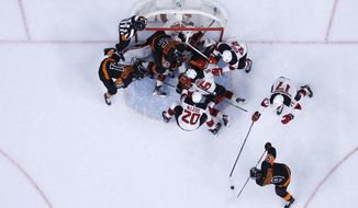Philadelphia Flyers' Ivan Provorov (9) tries to get a shot past New Jersey Devils' Yegor Sharangovich (17) during the second period of an NHL hockey game, Sunday, April 25, 2021, in Philadelphia. (AP Photo/Matt Slocum)