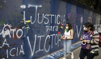 """Young women bring flowers to the perimeter wall of the Quintana Roo state offices sprayed with graffiti that reads in Spanish """"Justice for Victoria,"""" during a protest in Mexico City, Monday, March. 29, 2021. The demonstrators were protesting the police killing in Tulum, Quintana Roo state, of Salvadoran national Victoria Esperanza Salazar when a female police officer knelt on her back to cuff her. Mexican authorities say an autopsy confirmed that police broke her neck. (AP Photo/Eduardo Verdugo)"""