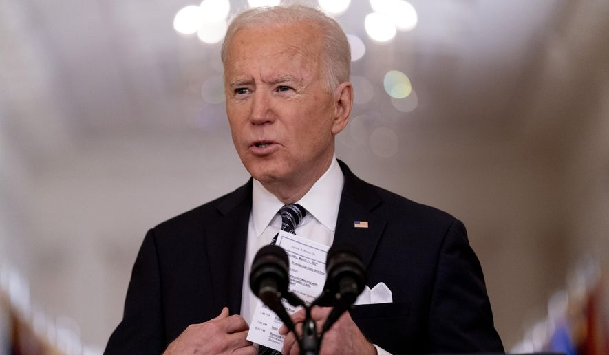 In this March 11, 2021, file photo President Joe Biden holds up a card with his daily schedule and the daily deaths from COVID-19 as he speaks about the COVID-19 pandemic during a prime-time address from the East Room of the White House in Washington. (AP Photo/Andrew Harnik, File)