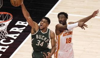 Milwaukee Bucks forward Giannis Antetokounmpo (34) scores past Atlanta Hawks forward Solomon Hill (18) during the first half of an NBA basketball game on Sunday, April 25, 2021, in Atlanta. (AP Photo/Ben Gray)