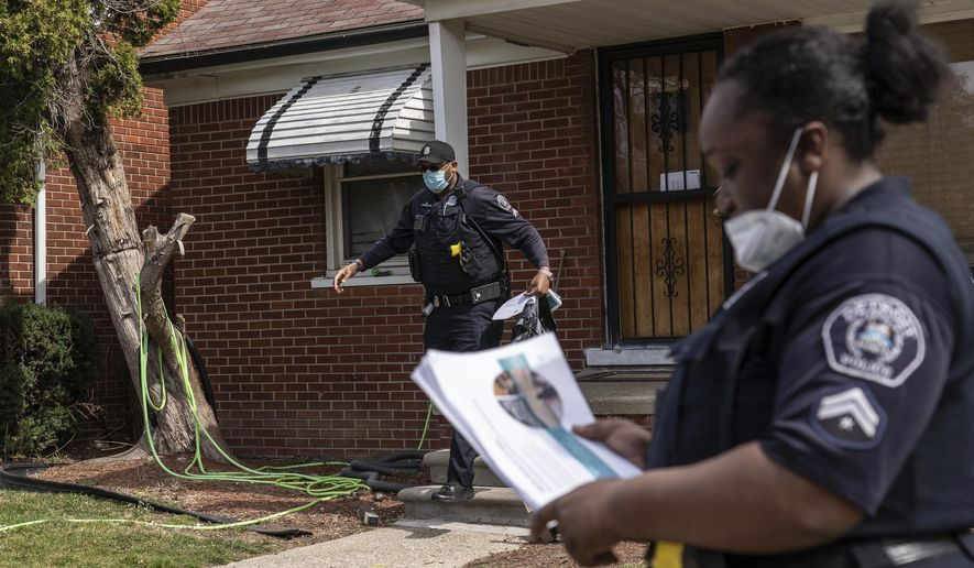 Detroit Police Department Neighborhood Police Officer Marcia Williams, right, organizes papers to deliver door-to-door with Detroit Police Department Neighborhood Police Officer Dan Robinson as they distribute gun safety information and gun locks to residents along Fenelon Street on Detroit's east side on Thursday, March 25, 2021. Residents said they feel safer in their neighborhoods with police presence and that the job of the Detroit Police Departments neighborhood police officers. (Ryan Garza/Detroit Free Press via AP)