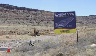 In this March 28, 2021, photo, a D.R Horton's developer's sign is posted at the existing exit for Long Valley Road showing plans for a new 2,100 single family homes and townhomes subdivision along the Southern Parkway near Sand Hollow Reservoir in Washington County, Utah. Conservationists are fighting plans to extend Long Valley Road south into desert tortoise habitat to provide a second entrance to the subdivision. (Joan Meiners/The Spectrum via AP)