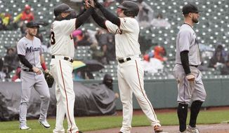 San Francisco Giants' Logan Webb, center, is congratulated by third base coach Ron Wotus after hitting a two-run triple against the Miami Marlins during the second inning of a baseball game in San Francisco, Sunday, April 25, 2021. Also pictured, at right, is Marlins third baseman Jon Berti. (AP Photo/Jeff Chiu)