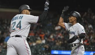 Miami Marlins' Jesus Aguilar (24) celebrates after hitting a two-run home run that also scored Magneuris Sierra, right, during the ninth inning of a baseball game against the San Francisco Giants in San Francisco, Saturday, April 24, 2021. (AP Photo/Jeff Chiu)