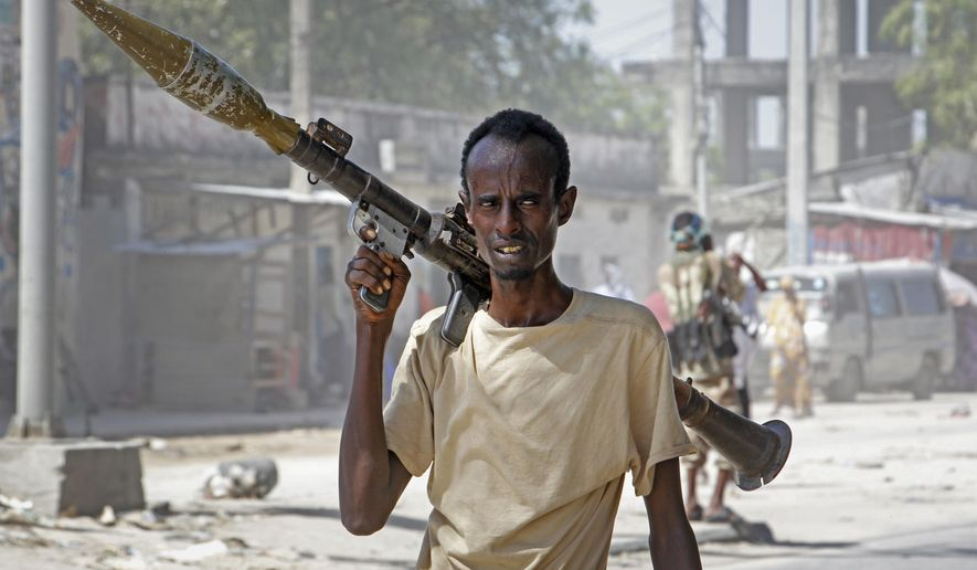 A soldier supporting anti-government opposition groups carries a rocket-propelled grenade launcher on a street in the Fagah area of Mogadishu, Somalia Sunday, April 25, 2021. Gunfire was exchanged Sunday between government forces loyal to President Mohamed Abdullahi Mohamed, who signed into law on April 14 a two year extension of his mandate and that of his government, and other sections of the military opposed to the move and sympathetic to former presidents Hassan Sheikh Mohamud and Sharif Sheikh Ahmed. (AP Photo/Farah Abdi Warsameh)