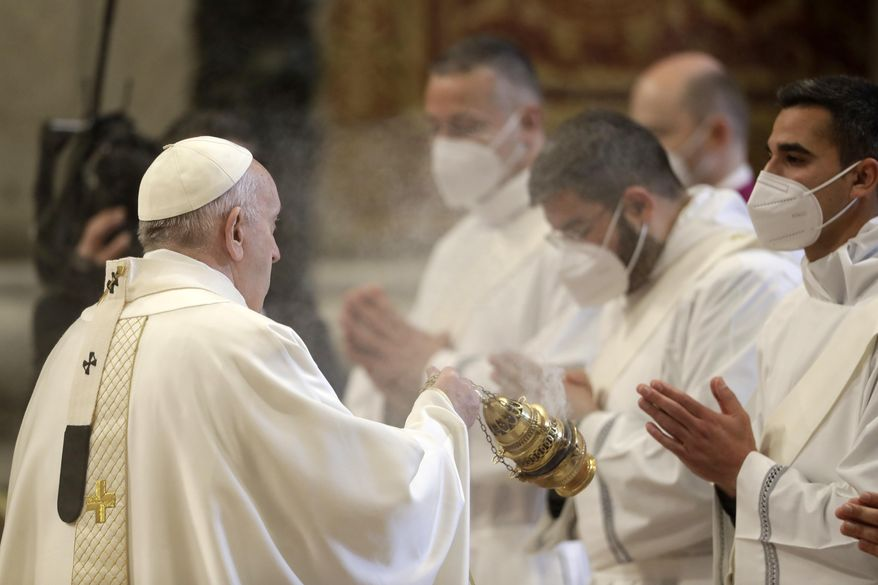 Pope Francis spreads incense during a ceremony to ordain nine new priests, standing in front of him and wearing face masks to curb the spread of COVID-19, inside St. Peter's Basilica, at the Vatican, Sunday, April 25, 2021. (AP Photo/Andrew Medichini)