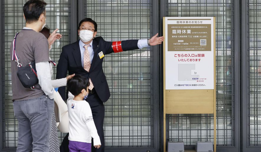 """An usher briefs visitors at an entrance of a department store which is open partially, in Tokyo Sunday, April 25, 2021. Japan's department stores, bars and theaters shuttered Sunday, as the government """"state of emergency"""" over the coronavirus pandemic kicked in amid growing worries about a surge in infections. (Hiroko Harima/Kyodo News via AP)"""