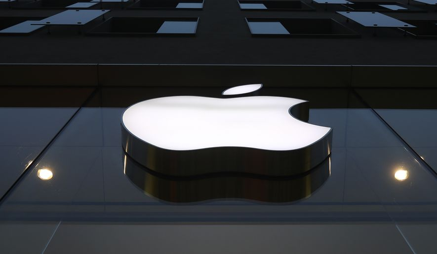 FILE - In this Wednesday, Dec. 16, 2020, file photo, the logo of Apple is illuminated at a store in the city center in Munich. On Monday, April 26, 2021, Apple announced plans to invest more than $1 billion in North Carolina to build the company's first East Coast campus, in a move that is expected to bring at least 3,000 new jobs to the state. (AP Photo/Matthias Schrader, File)