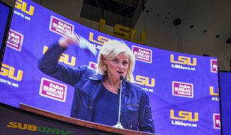 """New LSU women's basketball coach Kim Mulkey flings off her mask, """"Because I've got a lot to say!"""" she said while speaking at an introductory NCAA college basketball news conference at the Pete Maravich Assembly Center in Baton Rouge, La., Monday, April 26, 2021. Mulkey returned to her home state, for what she said was the only job that could get her to leave Baylor, which she and her staff have built into a national women's basketball powerhouse. (Travis Spradling/The Advocate via AP)"""