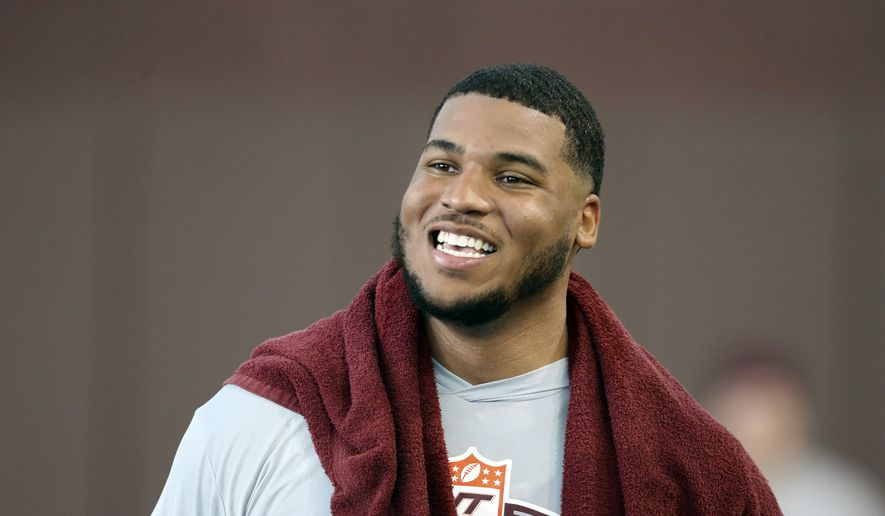 FILE - Christian Darrisaw smiles after completing a set of offensive line drills during Virginia Tech Pro Day in Blacksburg, Va., in this Friday, March 26, 2021, file photo. Darrisaw is a possible first round pick in the NFL Draft, April 29-May 1, 2021, in Cleveland. (AP Photo/Matt Gentry, File) **FILE**