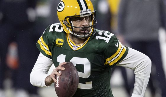 """In this Jan. 16, 2021, photo, Green Bay Packers quarterback Aaron Rodgers (12) runs during an NFL divisional playoff football game against the Los Angeles Rams in Green Bay, Wis. Packers general manager Brian Gutekunst says the team remains committed to Rodgers """"for the foreseeable future"""" one year after trading up in the first round to draft the three-time MVP's potential successor. (AP Photo/Jeffrey Phelps) **FILE**"""